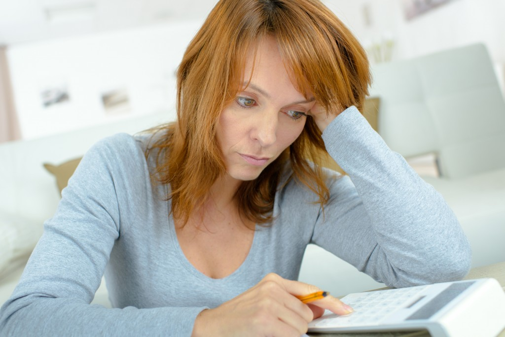 Lady using calculator, stressed