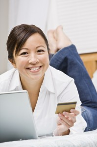 Beautiful asian woman holding a credit card and using a laptop.