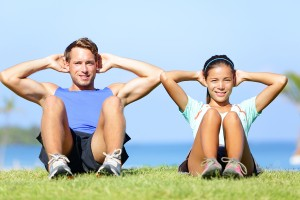Sit ups - fitness couple exercising sit up outside in grass in s