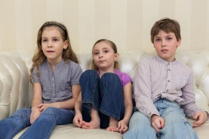 Three children sitting on a sofa and watching TV