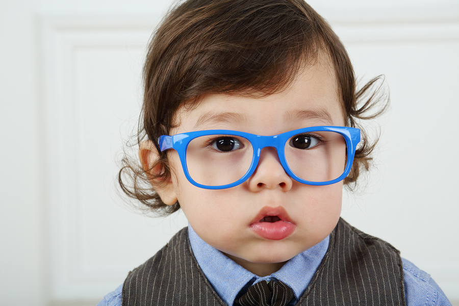 Portrait of serious little boy with big brown eyes and blue glas