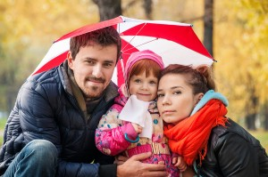 Happy Young Family Under An Umbrella In An Autumn Park