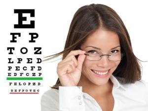 Optician or optometrist wearing glasses standing by Snellen eye
