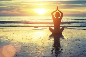 Silhouette of yoga woman meditating on the ocean beach. Fitness.