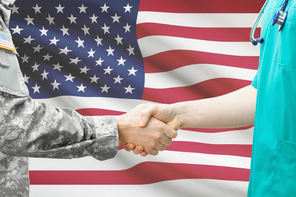 Soldier And Doctor Shaking Hands With Flag On Background - Unite